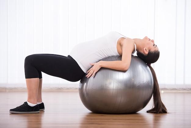 A menina grávida estica para trás na esfera para a aptidão.