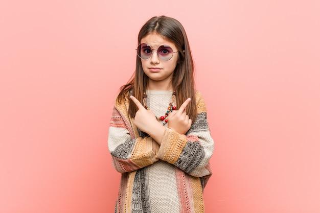 A menina hippie aponta de lado, está tentando escolher entre duas opções.