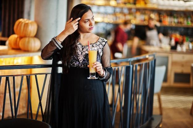 A menina indiana bonita no vestido preto do saree levantou no restaurante com suco de laranja à mão.