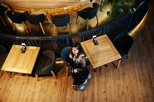 A menina indiana bonita no vestido preto do saree levantou no restaurante. vista de cima.