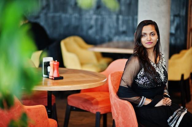 A menina indiana bonita no vestido preto do saree levantou no restaurante.
