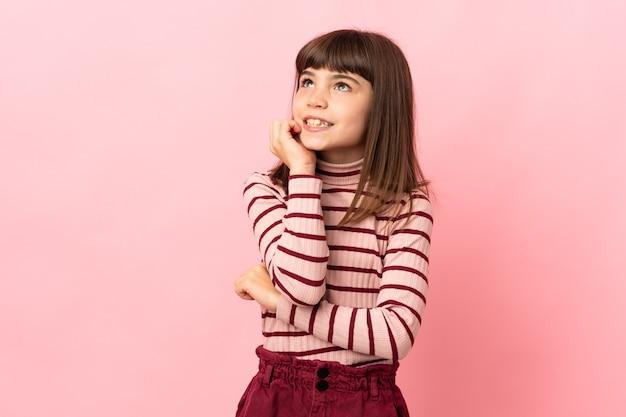 A menina isolada na parede rosa está um pouco nervosa