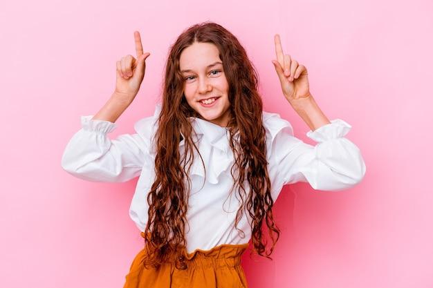 A menina isolada na parede rosa indica com os dois dedos indicadores para cima mostrando um espaço em branco