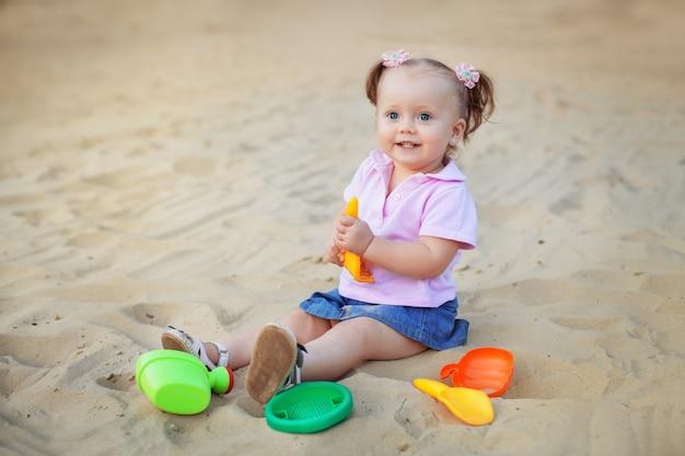 A menina joga com os brinquedos na areia.