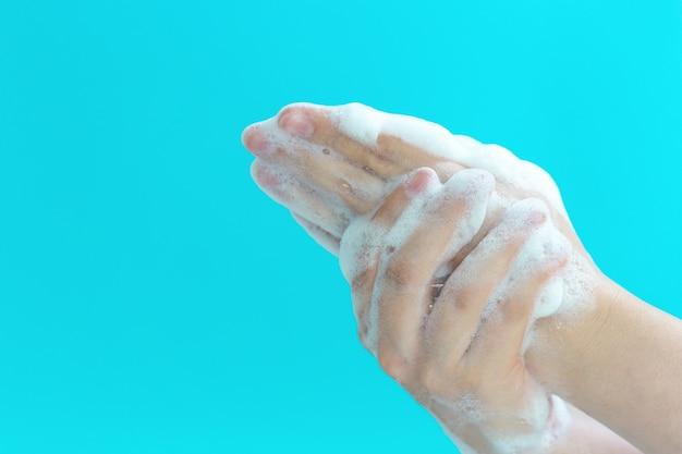 A menina lava as mãos com sabão e espuma sobre um fundo azul, vista lateral