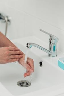A menina lava as mãos para evitar a infecção pelo vírus covid-19.