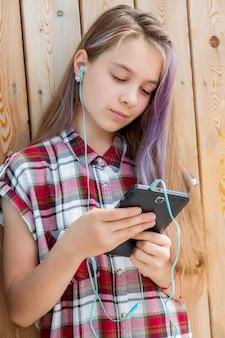 A menina lê uma mensagem em um telefone celular. conceito de crianças e gadgets. comunicação com amigos