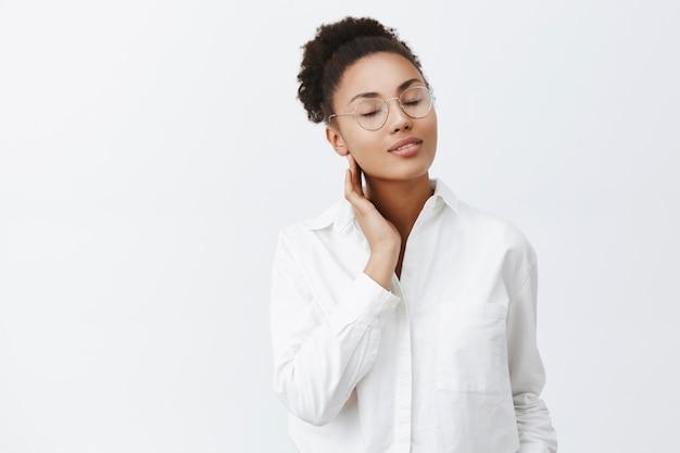 A menina lembra do beijo apaixonado do amante. retrato de uma terna mulher afro-americana feminina de óculos e camisa branca, fechando os olhos e tocando o pescoço suavemente, em pé sobre uma parede cinza