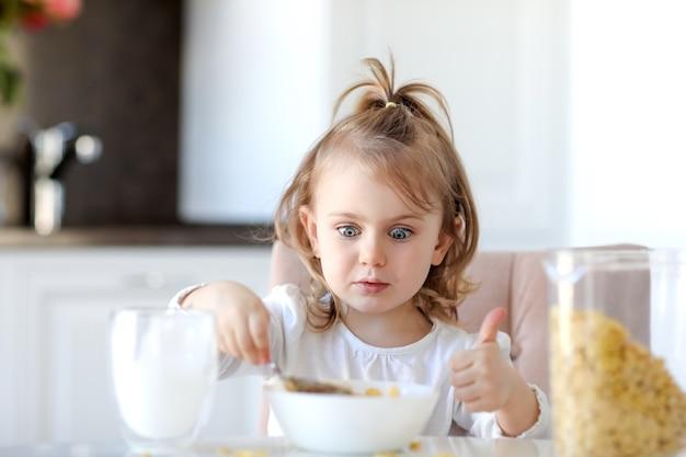 A menina linda criança toma café da manhã e fica surpresa com o prato com flocos de milho e leite