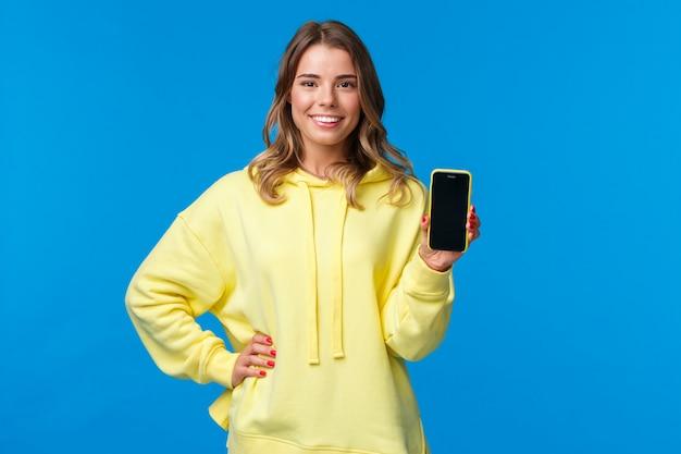 A menina loira bonita de cintura alta retrato com capuz amarelo promove o aplicativo para smartphone, mostra a tela do telefone móvel e sorri como recomendar assinar ou baixar o aplicativo