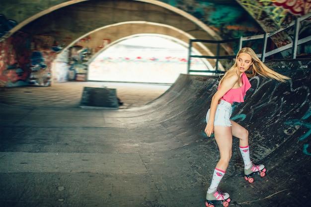 A menina loira bonita e bem construída anda de patins na sala de treinamento especial. ela está caindo para trás. menina está olhando para trás com uma visão séria. ela está concentrada.