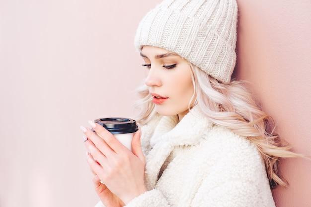 A menina loira em roupas de inverno está segurando um café em um copo de papel em um fundo rosa.