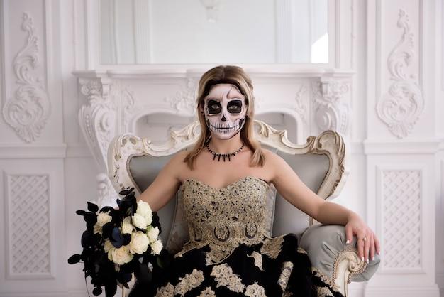 A menina loura com crânio do açúcar faz dia dos mortos ou dia das bruxas