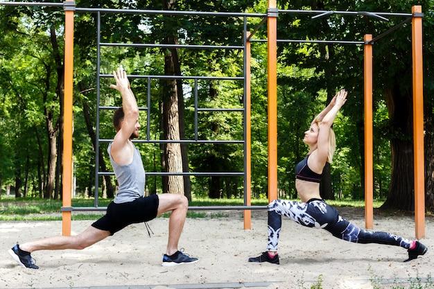 A menina loura desportiva e o homem farpado estão aquecendo-se antes de treinar em um parque exterior.