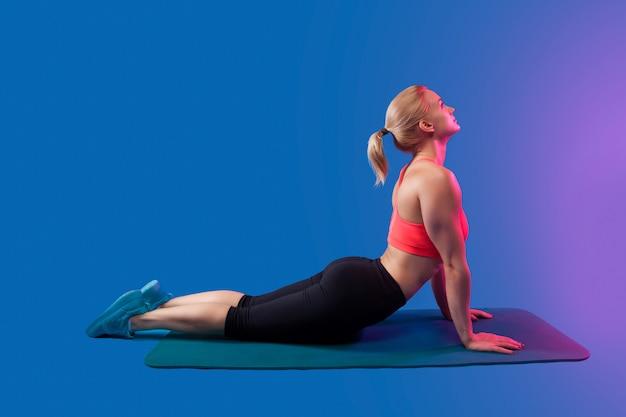 A menina loura é acoplada no esticão em um tapete de ioga azul em um fundo azul.