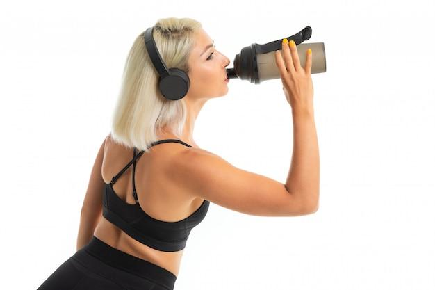 A menina loura em um uniforme de esportes bebe a água escuta a música