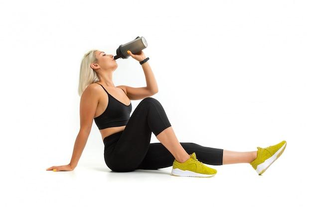 A menina loura em um uniforme preto dos esportes bebe a água que senta-se no branco isolado assoalho