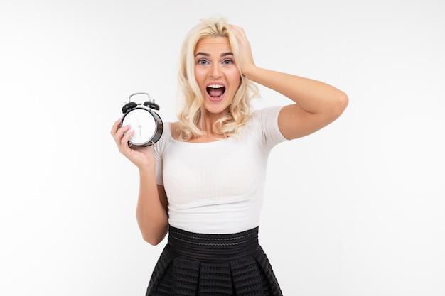 A menina loura em uma camiseta branca prende um despertador em um fundo branco com espaço da cópia