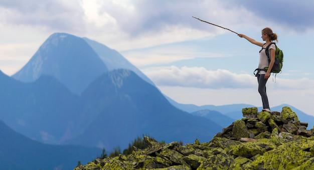 A menina loura magro nova do turista com trouxa aponta com a vara no panorama nevoento da cordilheira que está na parte superior rochosa no céu azul brilhante da manhã. conceito de turismo, viagens e escalada.