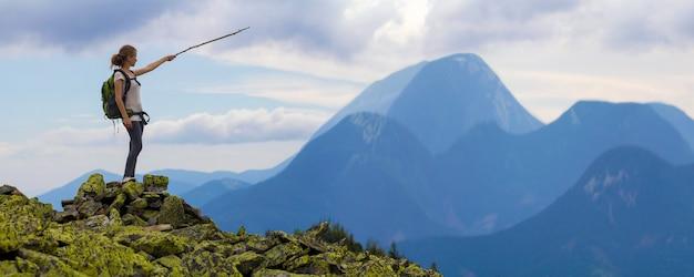 A menina loura magro nova do turista com trouxa aponta com a vara no panorama nevoento da cordilheira que está na parte superior rochosa no fundo azul brilhante do céu da manhã. conceito de turismo, viagens e escalada.