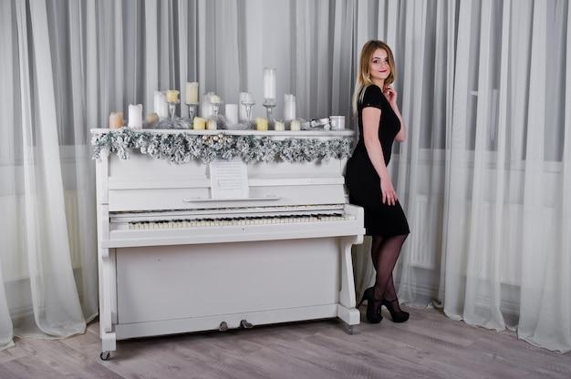 A menina loura no vestido preto levantou perto do piano com a decoração das velas do natal na sala branca.