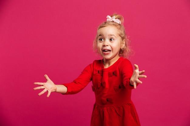 A menina loura nova da beleza no vestido vermelho quer abraços