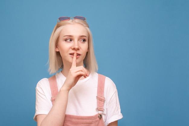A menina loura positiva em roupas brilhantes mostra um sinal de silêncio e olha de lado em um fundo azul