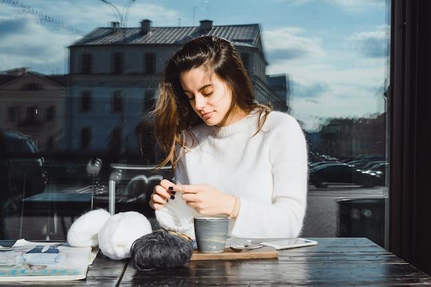 A menina malha em um café