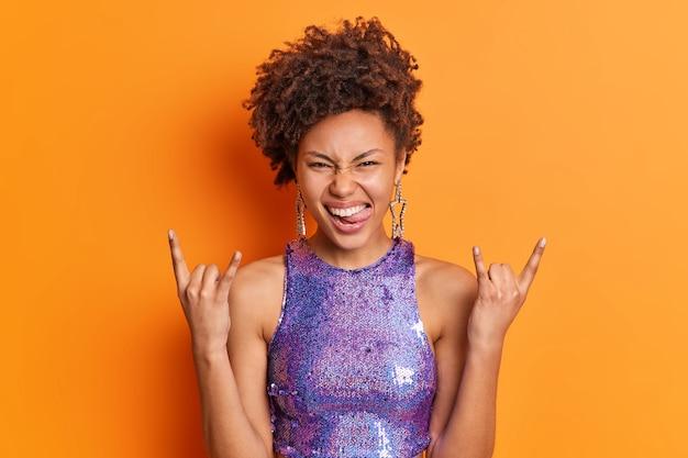A menina milenar positiva com cabelo afro mostra a língua fazendo gestos de rock n roll chifres com os dedos e se diverte ouvindo músicas favoritas na festa