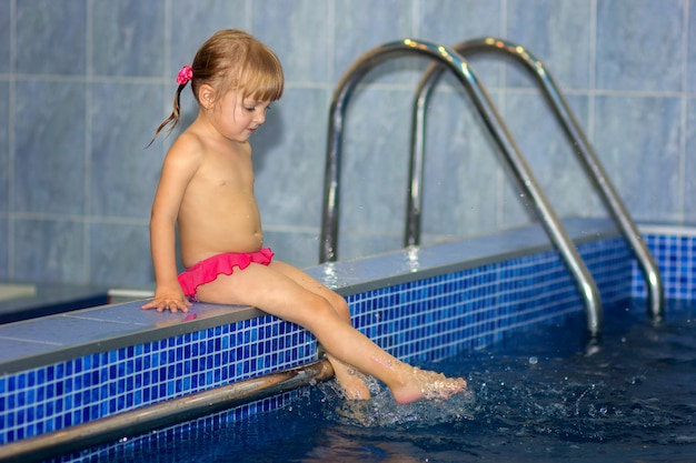 A menina molha as pernas na piscina