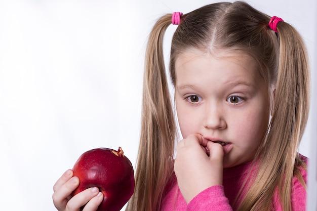 A menina mordeu uma grande maçã vermelha e danificou o dente