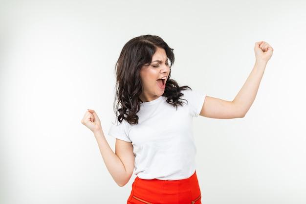 A menina morena dançando em uma camiseta branca sai música isolada em um fundo branco