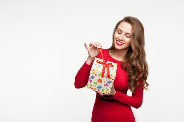 A menina morena está segurando um presente e rindo