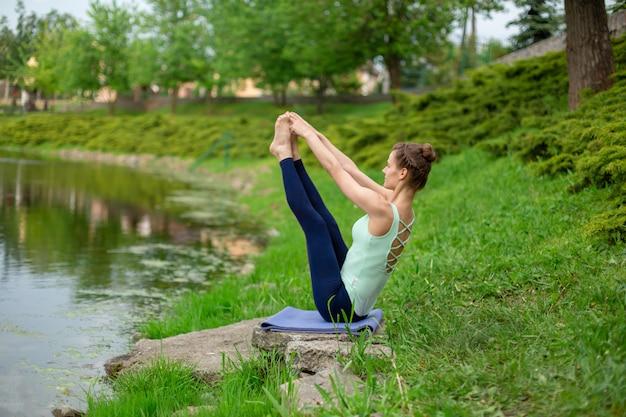 A menina moreno fina que senta-se em ambos o dedão do pé exercita, paripurna navasana levanta em um parque do verão. mulher fazendo exercícios no tapete de ioga