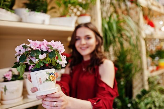 A menina moreno na compra vermelha floresce na loja de flor.