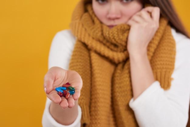 A menina moreno tem o frio, poses com os comprimidos isolados.