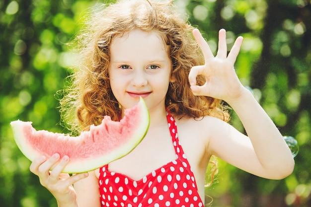 A menina mostra o gesto aprovado e que come a melancia.