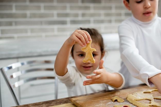 A menina mostra o preparo do biscoito em forma de homem