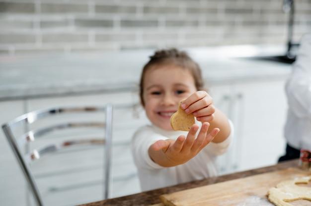 A menina mostra para a câmera um coraçãozinho da massa e sorri