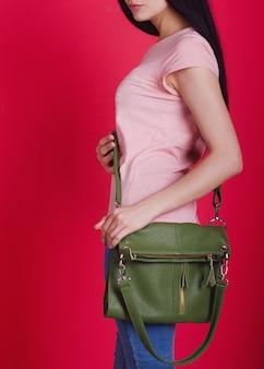 A menina mostra uma elegante bolsa feminina de couro. acessório feminino requintado. anúncio de bolsa de senhora