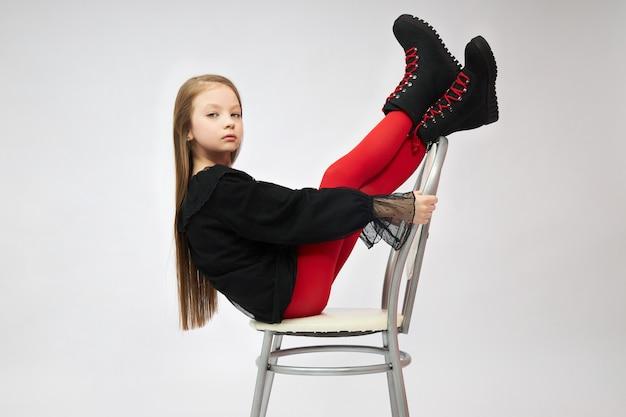 A menina na bota da mola calça o levantamento no estúdio em um branco.