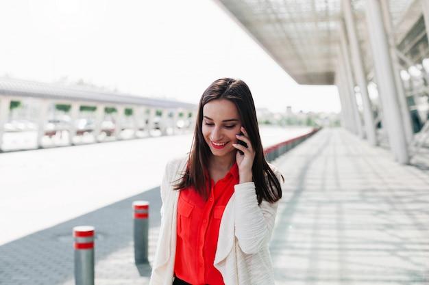 A menina na camisa vermelha fala no telefone lá fora