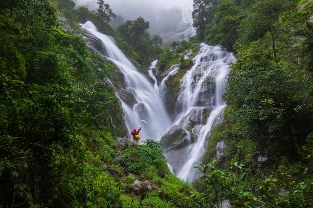 A menina na camisola vermelha que visita na cachoeira do pi-tu-gro, cachoeira bonita na província de tak, thailand.