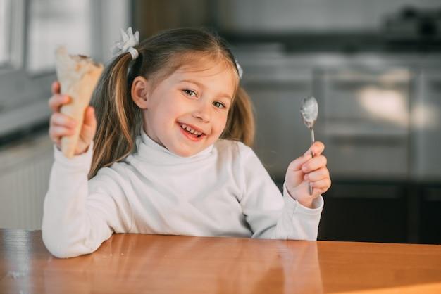 A menina na cozinha comendo a casquinha de sorvete com uma colher a luz do dia muito doce