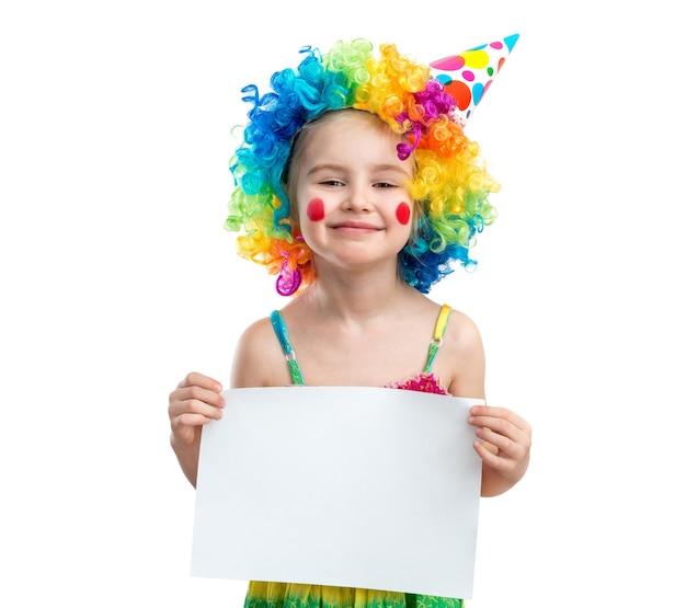 A menina na peruca do palhaço prende o papel em branco, isolado no fundo branco
