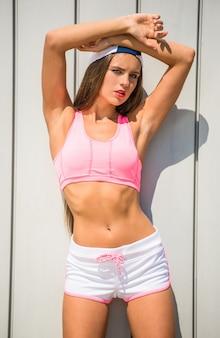 A menina na roupa dos esportes está levantando de encontro à parede ao ar livre.