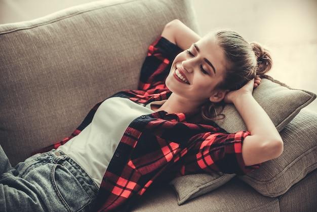 A menina na roupa ocasional está sorrindo ao encontrar-se no sofá