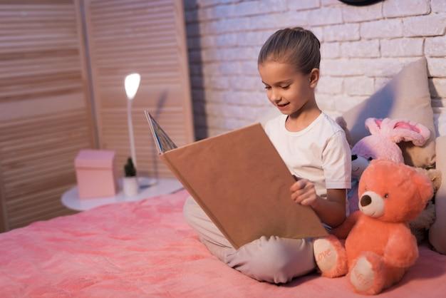 A menina, neta está lendo o livro na noite em casa.