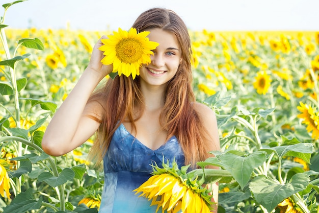 A menina no campo do girassol, menina emocional, adolescente alegre da beleza com girassol, sol irradia, raios do sol, sol de incandescência. iluminado.