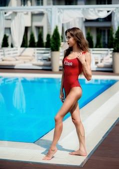 A menina no maiô vermelho está de pé pela piscina azul